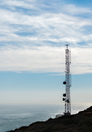 steel tower: Backlit silhouette of cell phone telecommunication tower overlooking the ocean.  Steel lattice structure. High contrast photo. High wispy clouds, blue sky. Copyspace. Verical composition.