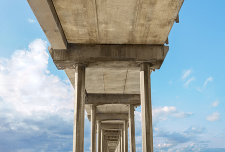 underneath: Under the bridge and sky with storm clouds.  Perspective view from underneath massive concrete structure. Stock Photo