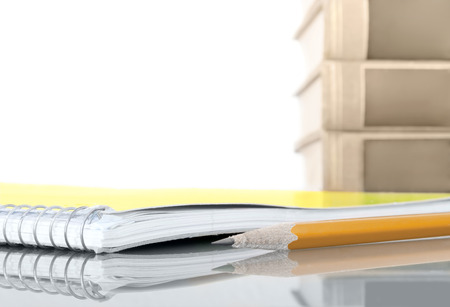 pencil point: Pencil and closed spiral notebook with reflection.  Shallow depth of field, focus on sharp pencil point. Blurred stack of books in background. Isolated on white.