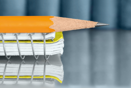 pencil point: Side of yellow wooden pencil and spiral wire notebook with reflection.  Shallow depth of field, focus on sharp pencil point. Low angle view on reflective surface. Row of blue books in blurred background.