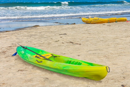 recreational sport: Bright green and yellow fiberglass canoe on sandy beach.  Small recreational sport boat with grab loop and carrying handles. Rolling ocean waves blurry background.