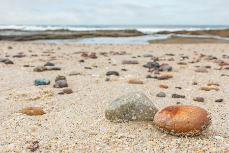 sandy beach: Small rocks scattered on beach sand close up.  Shallow depth of field. Selective focus on foreground rocks. Blurred background of many multicolor stones of different shapes and sizes, ocean waves and overcast sky.