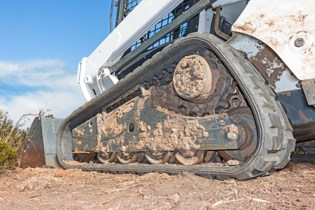 mini loader: Small track loader tractor crawler on dirt, low angle perspective view.  Small earth mover machine. Dirty undercarriage. Close up of roller, sprocket, and tread. Blue sky and clouds background.
