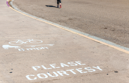 a courtesy: Bike, , and skateboard paved path speed limit.  White painted letters and symbols on pavement for safety and courtesy to pedestrians. Blurred jogger with shadow in background. Stock Photo