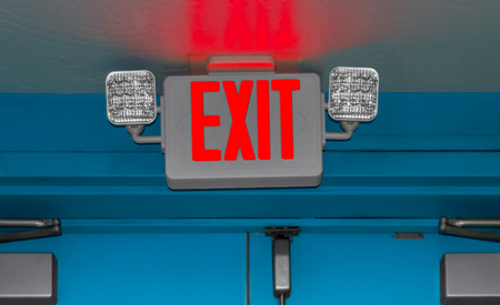 evacuate: Interior door emergency exit sign and lights.  Selective focus on the red exit letters and bulbs, blurred background. Dimly lit doorway. Bright red glow of the lit letters on the wall.