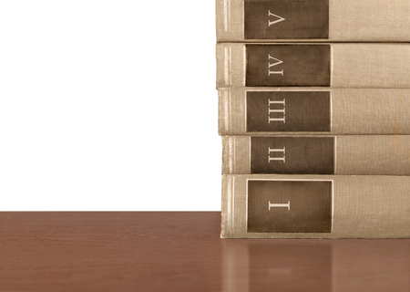 volumes: Stack of five old hardcover books on wood table.  Brown cloth texture volumes with Roman numerals 1 to 5 on spine. Isolated on white background, copy space.