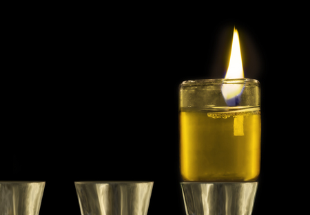 chanukah: Close up of one light lit on Chanukah oil menorah.  Floating wick and brightly burning flame in glass cup. Isolated on a black background.