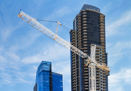revitalization: San Diego, California, USA - Jan. 15, 2016: Construction tower crane in front of tall commercial buildings as part of downtown revitalization Editorial
