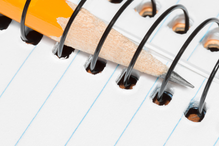 ruled paper: Yellow wooden pencil inserted in open spiral wire notebook.   Ruled paper with blue lines. Close up view.