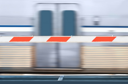 speeding: Red and white striped train crossing barrier and speeding urban commuter train.