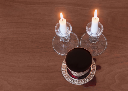 kiddush: Shabbat silver kiddush cup and two lit candles on wood texture background.