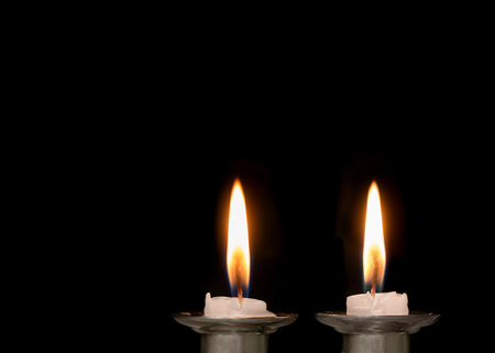 shabat: velas de Shabat jud�o quema baja. Dos velas de Shabat encendidas de fusi�n. Espacio de la copia. Aislado en un fondo negro.