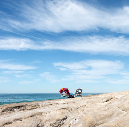 wispy: Two empty beach chairs on rocky cliff overlooking the calm ocean.  Blue sky and wispy clouds background. Square composition.