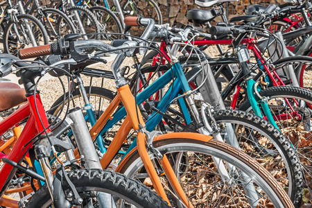 handlebars: Bicycle parking area with group of colorful bicycles parked together on gravel and dry leaves.   Shallow depth of field, focus on foreground bike tires and handlebars. Close up view.