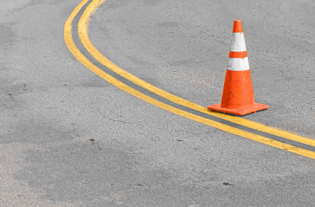 curving lines: Orange traffic cone on curving double yellow lines.  Stained gray rough asphalt surface.