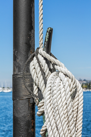 cleat: Nautical rope tied to vertical metal cleat on black pole.  Blue water and sky in blurred background.