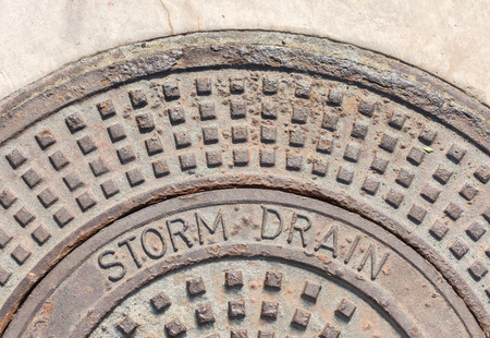 bumpy: Industrial outdoor metal storm drain in concrete.  Top half of large heavy round brown metal cover with words Storm Drain. Rough bumpy texture. Close up view. Stock Photo