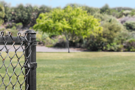 chain link fence: End of a black metal chainlink fence post in a public park.  Grassy field and trees in blurry background. Copy space.