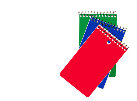 jot: 3 small spiral wire perforated notebooks isolated on a white background.  Red blue and green color covers. Handy compact size for ideas and quick notes. Copy space.