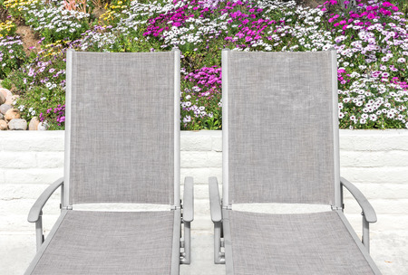 back cloth: Two outdoor lounge chair recliners, colorful daisy flowers and stone wall background.  Metal handrest, cloth back and seat.