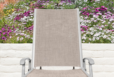 back cloth: Outdoor lounge chair, colorful daisy flowers and stone wall background.  Metal handrest, cloth back and seat.