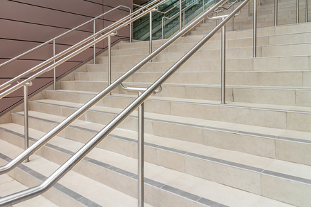 handrails: Urban interior concrete tile stairs with sets of dual metal handrails.  Blurry escalator in background. Stock Photo