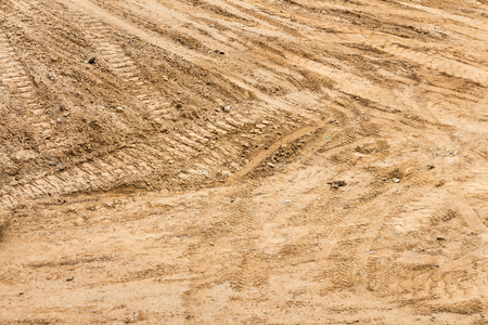 top down: Construction dirt with tractor tracks and tire tread marks crisscrossing the surface.  Sandy soil, top down view.