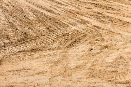 suelo arenoso: la suciedad de la construcci�n con pistas de tractor y marcas de rodadura de neum�ticos que cruzan la superficie. El suelo arenoso, vista de arriba abajo.