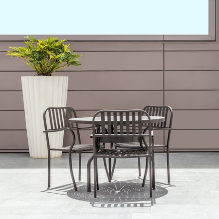 round chairs: Minimalist interior with metal patio table and chairs on tile floor.