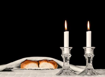 shabat: velas de Shabat en candelabros de cristal aislado en negro. fondo borroso de pan jal� cubierto en bandeja de plata en el mantel blanco. Copyspace. Foto de archivo