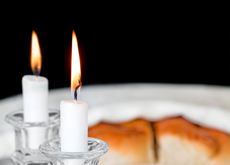 shabat: velas de Shabat en candelabros de cristal con fondo borroso jal� cubierta. Poca profundidad de campo de cerca. Centrarse en la llama de una vela delantera y mecha. Copyspace. Aislado en un fondo negro. Foto de archivo