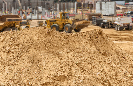 building foundation: Construction dirt pile at new development worksite.  Mound of sandy soil, rocks, and pebbles. Blurred loader vehicle, new building foundation and concrete pylons in background. Stock Photo