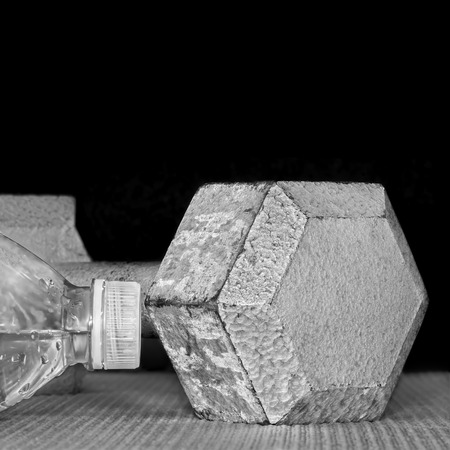 free weight: Gray metal hex dumbbell and water bottle on exercise mat isolated on a black background. Black and white photo. Free weight close up detail of chipped pitted and peeling textured surface. Copy space. Square composition.