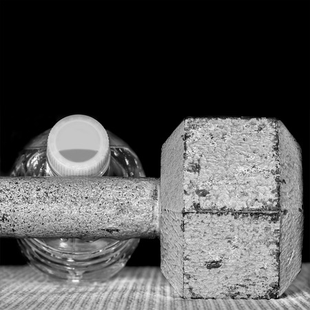 free weight: Gray metal hex dumbbell and water bottle isolated on a black background.  Black and white photo. Free weight close up detail of chipped pitted and peeling textured surface. Copy space. Square composition.