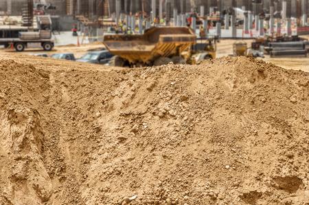 suelo arenoso: Construcci�n mont�n de tierra en el lugar de trabajo. Mont�culo de tierra arenosa, rocas, guijarros y. borrosa cami�n volcado y nuevos cimientos del edificio y pilones de hormig�n en el fondo.