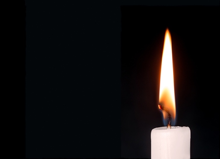 white candle: Close up detail of white wax lit candle flame and wick on isolated black background.  Copy space.