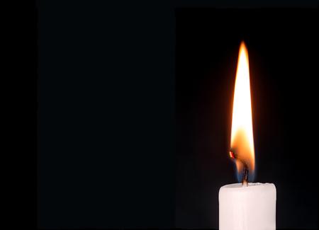 candela: Primo piano dettagliato di bianco cera candela accesa la fiamma e stoppino su sfondo nero isolato. Copia spazio.
