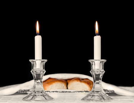candle holder: Shabbat candles in glass candlesticks.  Blurry background of covered challah bread in silver tray on white tablecloth. Isolated on black. Copyspace.