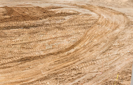 ground: Construction dirt with tractor tracks and tire tread marks across the surface.  Sandy soil, top down view.