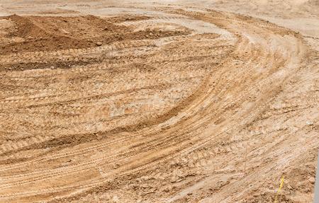 suelo arenoso: la suciedad de la construcci�n con pistas de tractor y marcas de rodadura de neum�ticos en toda la superficie. El suelo arenoso, vista de arriba abajo. Foto de archivo