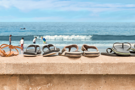 stone wall: Sandals lined up on a stone wall ledge at the beach.  Blurry background of children playing in the water, rolling foam waves, blue cloudy sky.