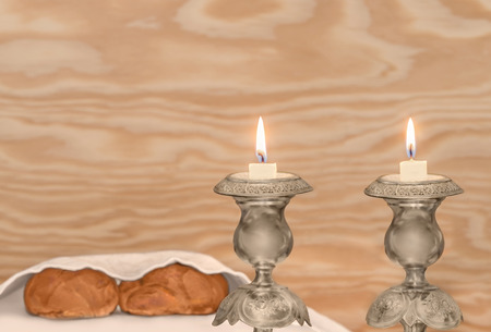 sabbath: Jewish sabbath antique metal candlesticks.  Lit candles burning low. Blurry covered challah bread loaves and wood grain background. Copy space. Stock Photo