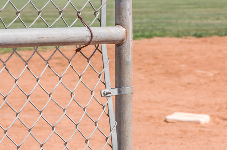 outfield: Amateur baseball field chain link fence gate.  Door opening to playing field. Blurred background of white base on red sandy infield and green outfield.