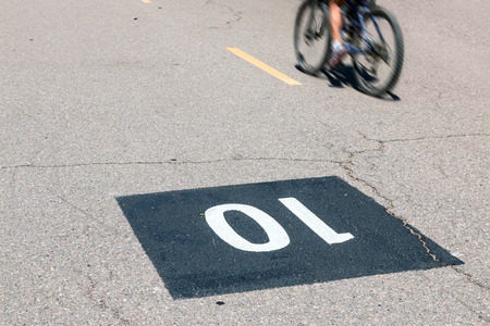 mph: Speed limit road marking on paved bike path.  10 mph max velocity in white paint upside down on black asphalt square. Motion blur of cyclist in background. Stock Photo