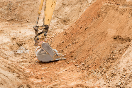 shovel in dirt: Construction excavator bucket working in dirt pit.  Shovel on rocky soil.