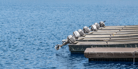 outboard: Row of small grey metal boats with outboard motors at rental dock.  Wooden jetty, calm blue water. Stock Photo