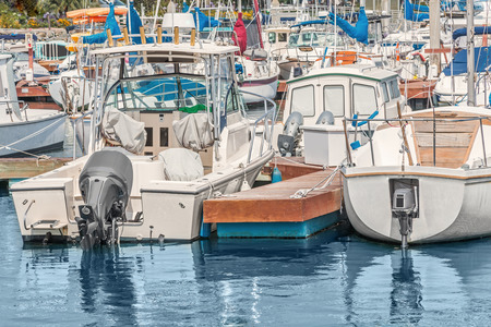 wooden dock: Motorboats tied to wooden dock at busy marina.  Reflections in the calm water. Stock Photo
