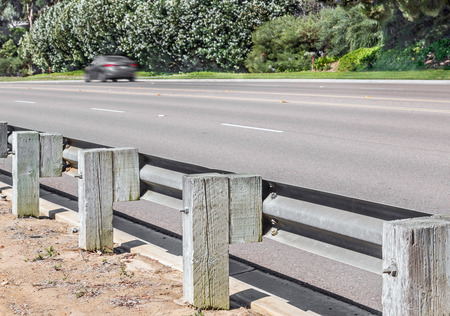 guard rail: Behind metal and wooden traffic guard rail barrier on dirt path along divided road.  Hard linear shadow on barricade gives depth and direction. Blurred motion car and bushes in background. Stock Photo