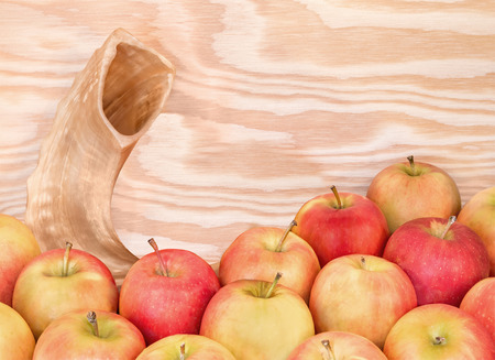 shul: Rosh Hashana shofar, whole red and yellow apples on wood grain background.  Jewish New Year traditional object and food.