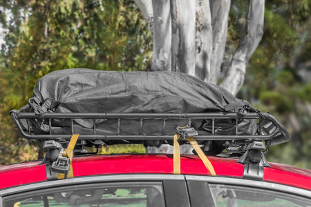 duffle: Black duffle bag on car roof rack .  Side view. Trees and foliage in blurred background. Stock Photo